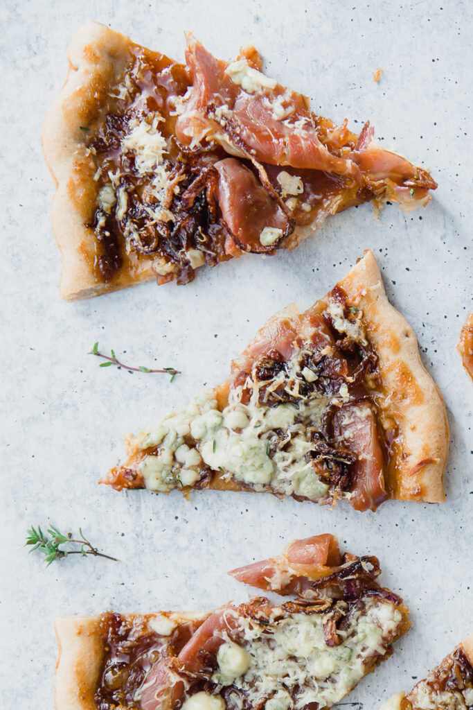 Up close look of Gorgonzola Fig Flatbread cut into triangles on a marble countertop