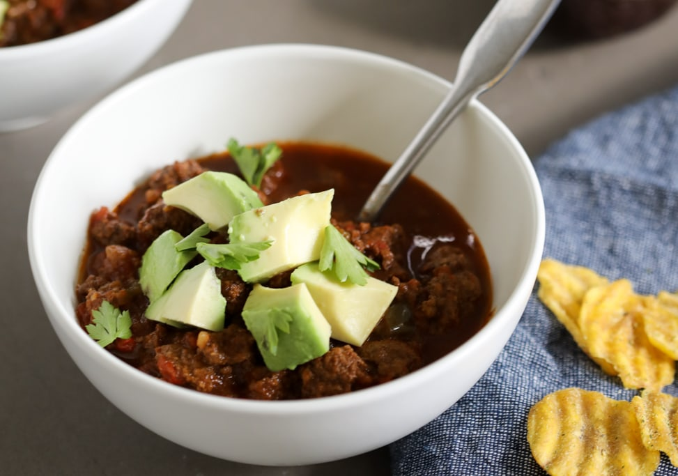 Instant Pot Option Chili Recipe with avocados on top in a bowl with cilantro and a spoon