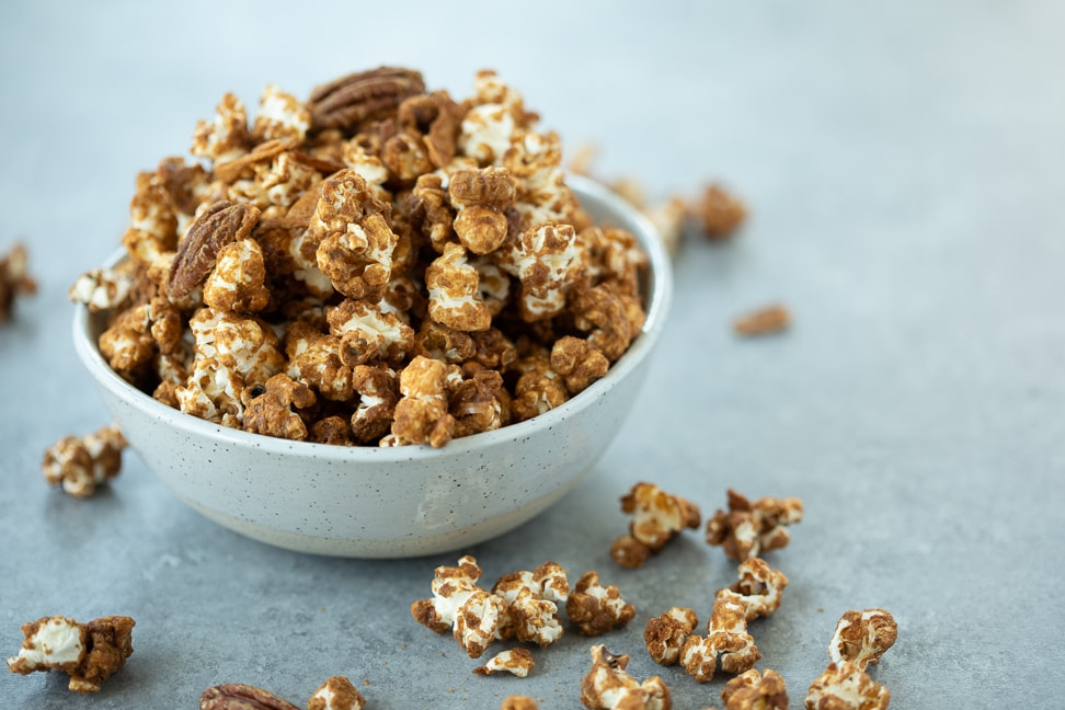 Gluten free caramel corn with pecans and coconut in a white bowl on a gray surface