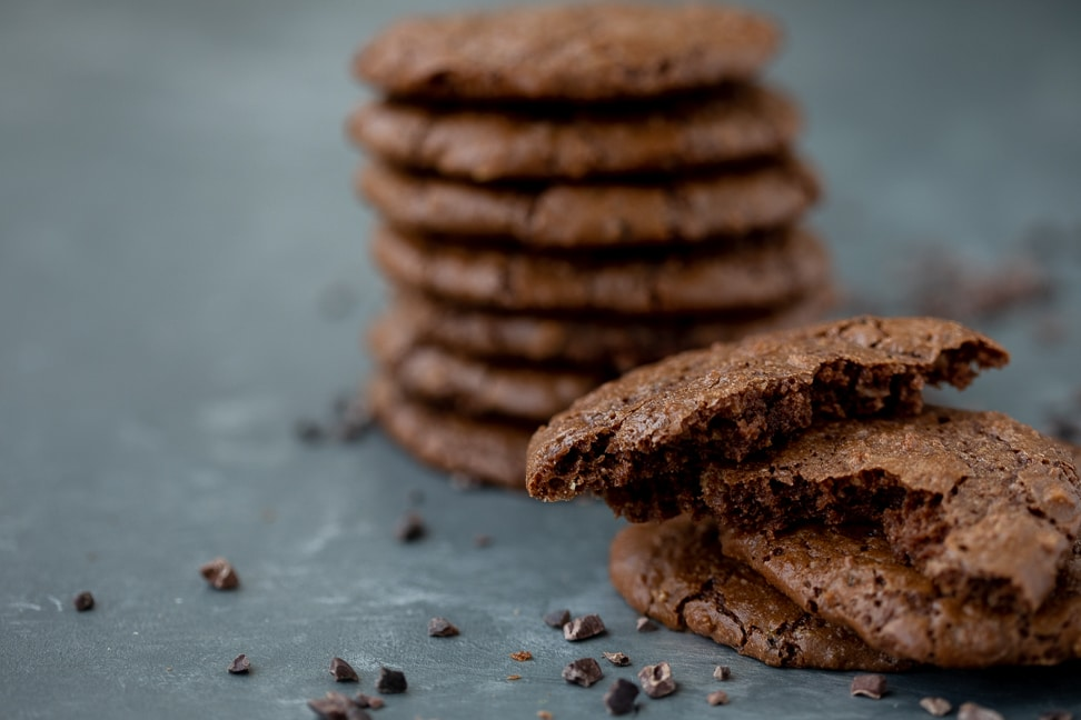 gluten free brownie corner cookies on a table stacked up seven high with several cookies in foreground half eaten