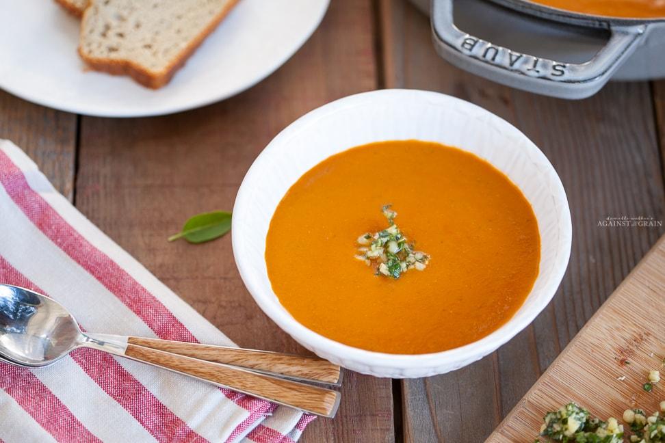 A bowl of steaming creamy tomato soup topped with pesto gremolata.