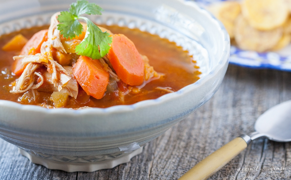 A steaming bowl of chicken enchilada soup topped with lime and cilantro!