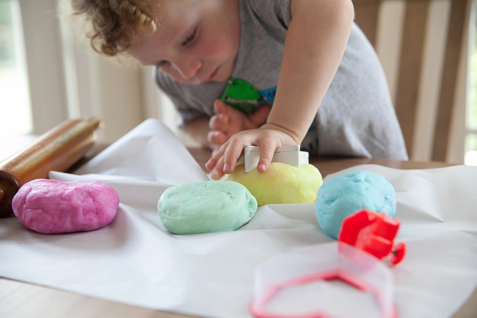 child making Natural Gluten Free Play Dough into shapes using a cookie cutter