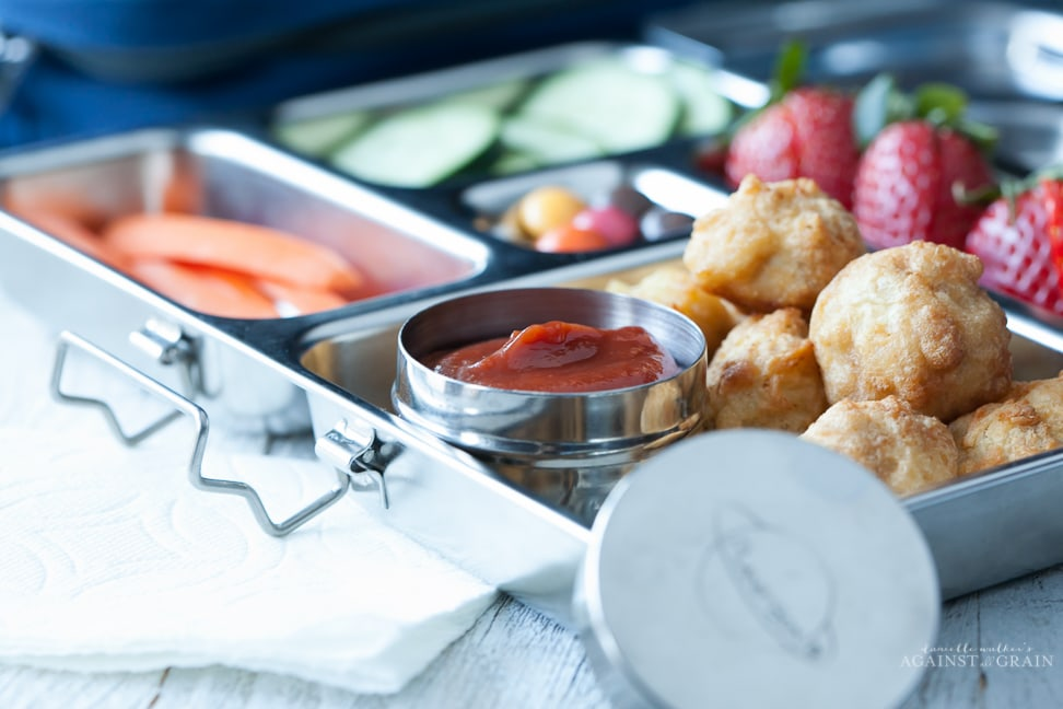 A lunch box filled with chicken nuggets, veggies, fruit and a container of homemade paleo ketchup. The ketchup is sweetened with dates and kid approved!