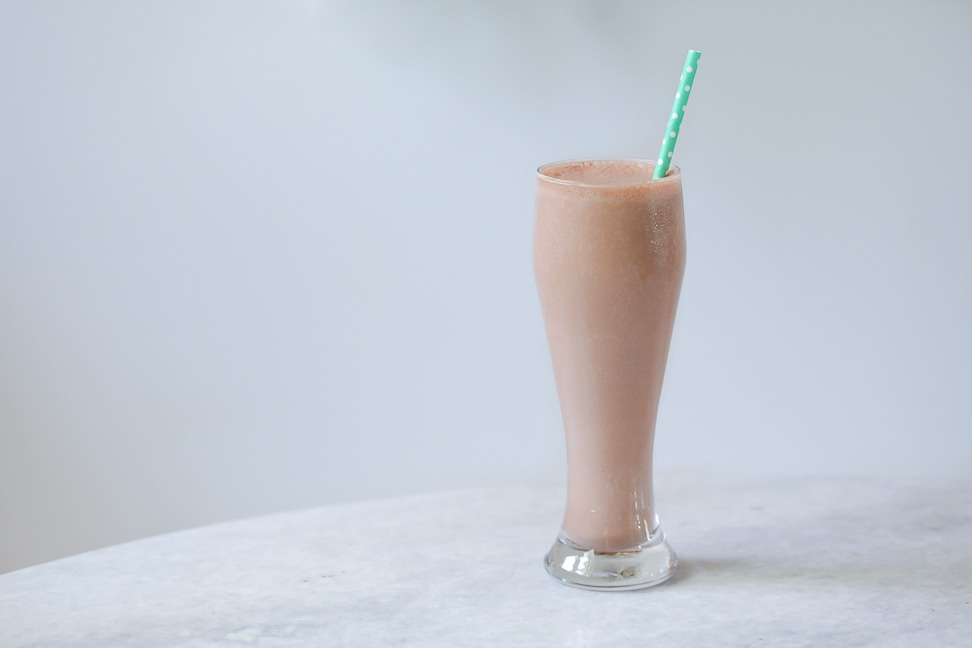 chocolate paleo protein shake in a glass with a green straw coming out of it