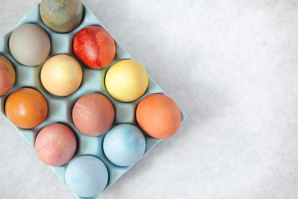 A tray of naturally dyed Easter eggs in hues of blue, yellow, orange and red.