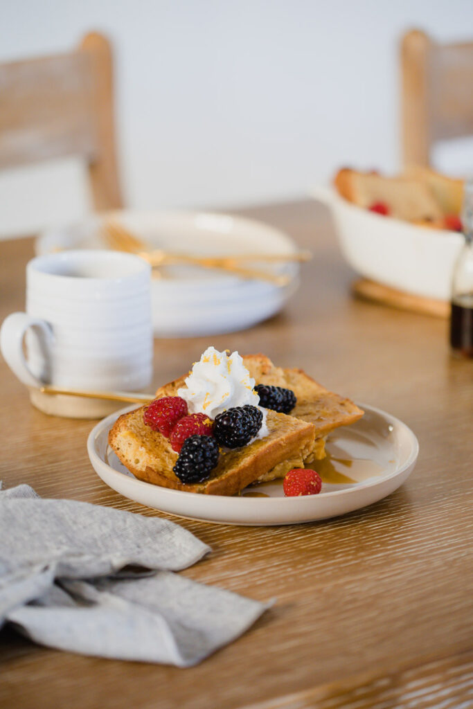 Meyer Lemon French Toast served on a white plate topped with whipped cream and fresh berries