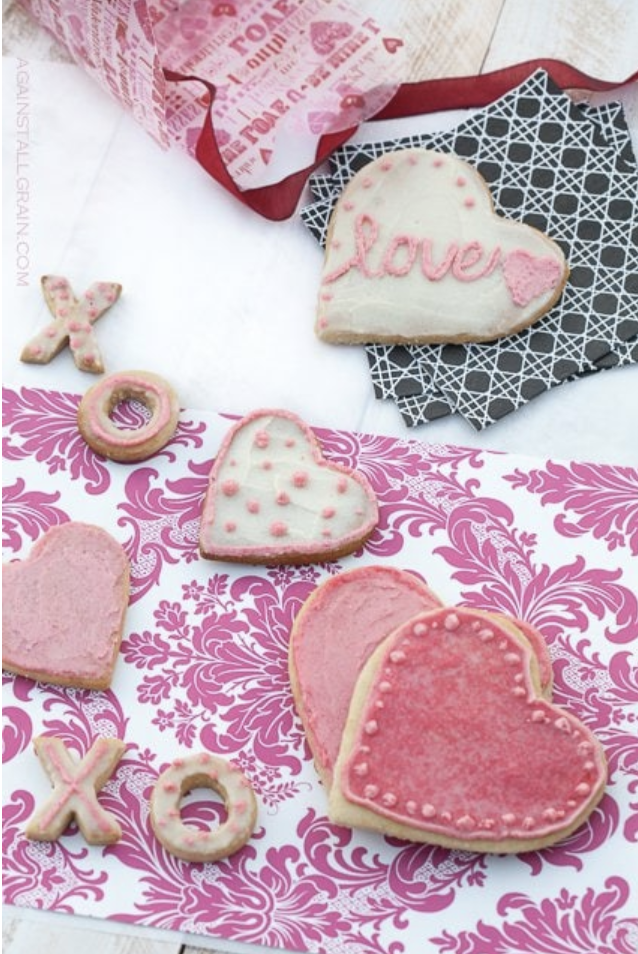 Variety of Valentine's Day themed gluten-free sugar cookies with white, red and pink icing