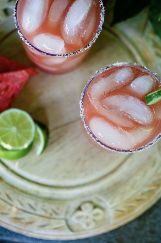 Watermelon Margaritas served in a glass over ice with lime garnishes