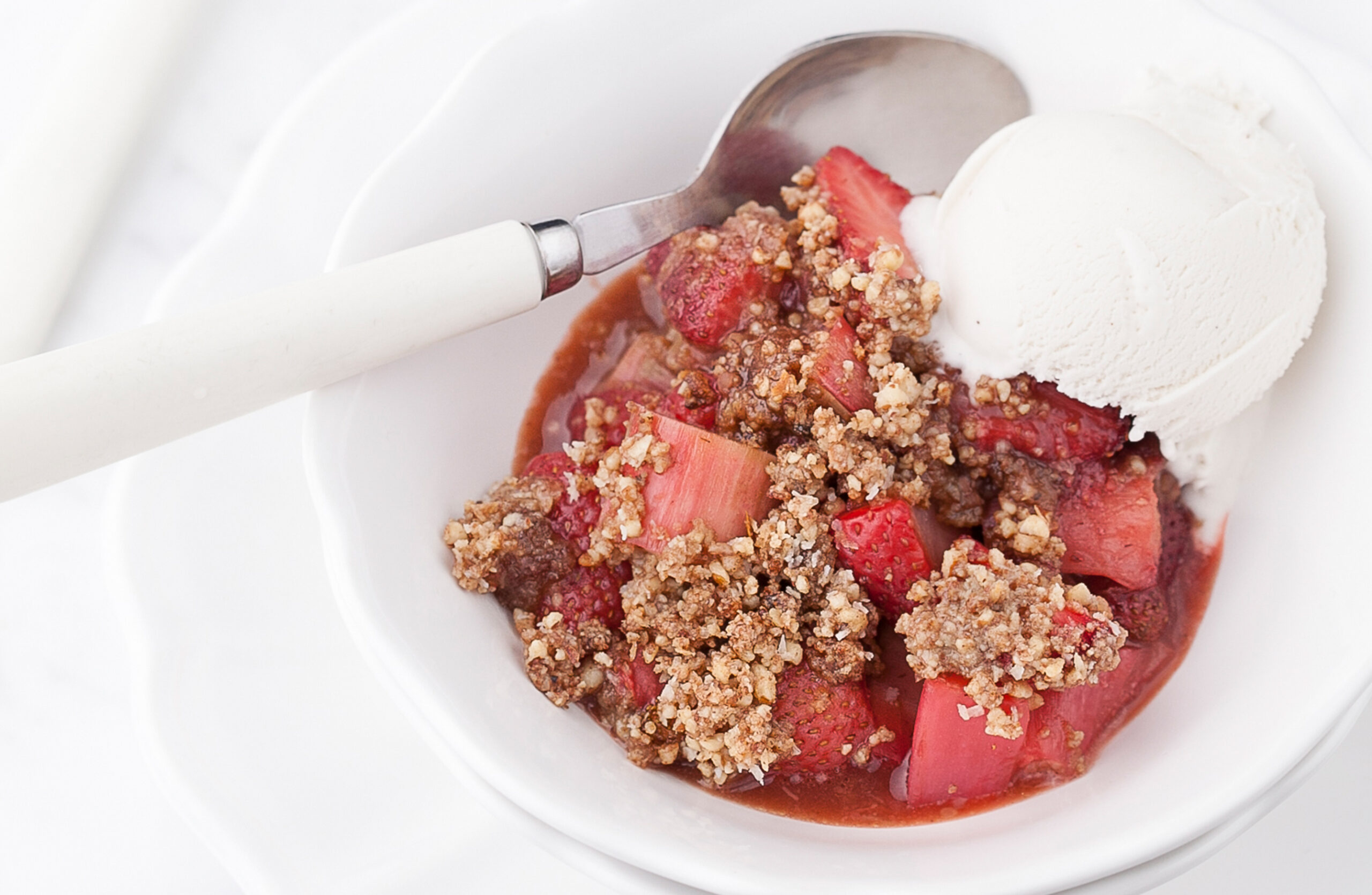 Gluten-Free Strawberry-Rhubarb Crisp in a white bowl topped with dairy free vanilla ice cream